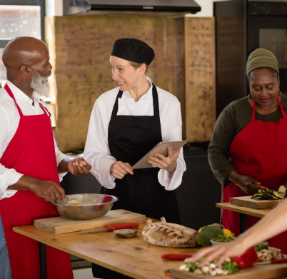 Side view of an Senior African American man and woman at a cookery class, listening to instructions from a Caucasian female chef wearing chefs whites and a black hat and apron, using a tablet computer while they work standing at a wooden table of ingredients